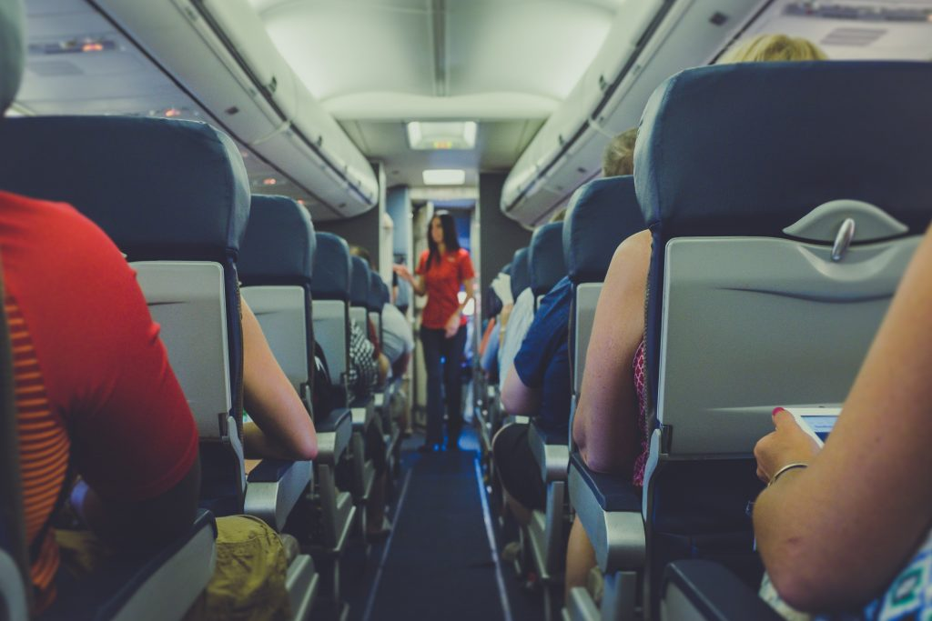 plane seats passengers aisle economy arms air stewardess